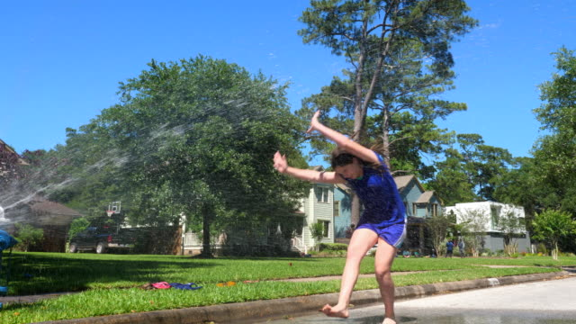ms teen girls doing cartwheels through spray from fire hydrant on summer afternoon - shorts stock-videos und b-roll-filmmaterial