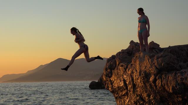 tonårsflickor som har kul på adriatiska kusten, hoppar från en sten i havet vid solnedgången och simma tillbaka till kusten - brant klippa bildbanksvideor och videomaterial från bakom kulisserna