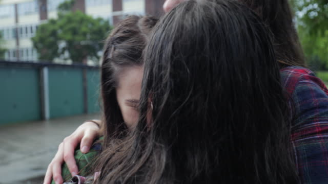 teen girls hugging in the rain - british culture stock videos & royalty-free footage