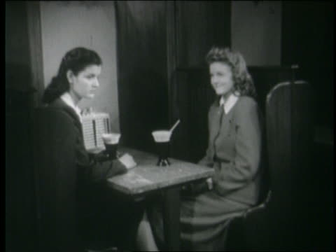 B/W 1946 2 teen girls in booth at malt shop as 2 boys go up to them