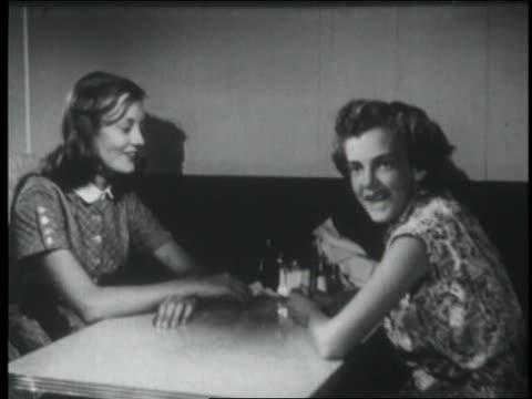vídeos y material grabado en eventos de stock de b/w 1953 2 teen girls in booth in soda fountain hiding faces - sólo chicas adolescentes