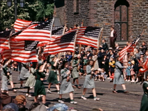 1940 teen girls in girl scout uniforms carrying us flags in parade / home movie - 1940~1949年点の映像素材/bロール