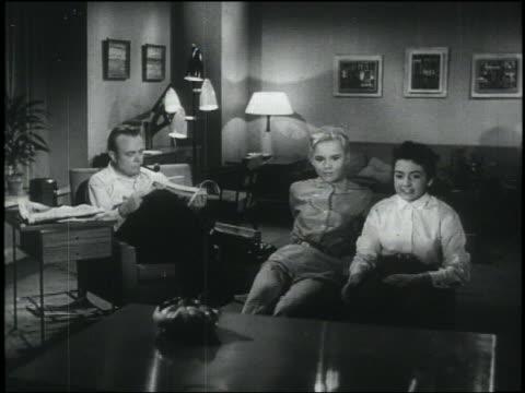 B/W 1956 2 teen girls lean toward television / man stops reading newspaper + looks at tv