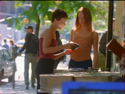 vidéos et rushes de 2 teen girls (1 black) looking at cds in boxes at stall on sidewalk / east village, nyc - 1990 1999