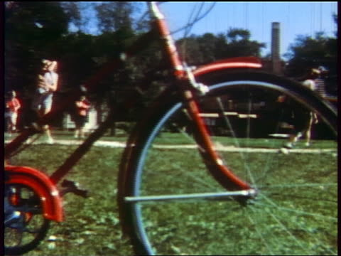 stockvideo's en b-roll-footage met 1957 teen girls running around bases as one girl tries to catch softball / bicycle in foreground - 1957