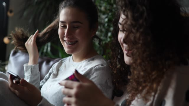 Teen girls using phone and smiling