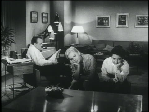 b/w 1956 2 teen girls watching tv sway dreamily to music / man stops reading paper, starts swaying - actor stock videos and b-roll footage