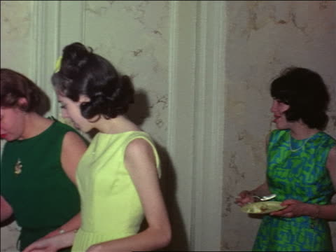 stockvideo's en b-roll-footage met 1963 teen girls + woman holding paper plates with birthday cake at party / home movie - 1963