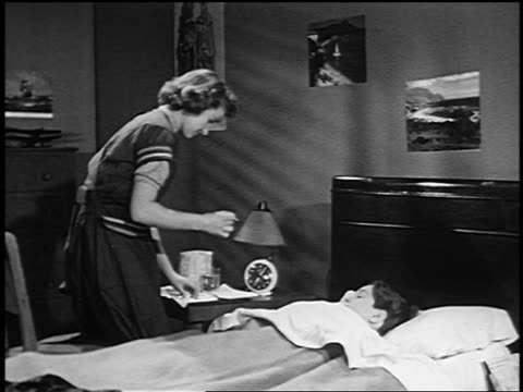 b/w 1953 teen girl/woman taking thermometer from boy lying in bed + wiping it with tissue - yorkville illinois stock videos & royalty-free footage
