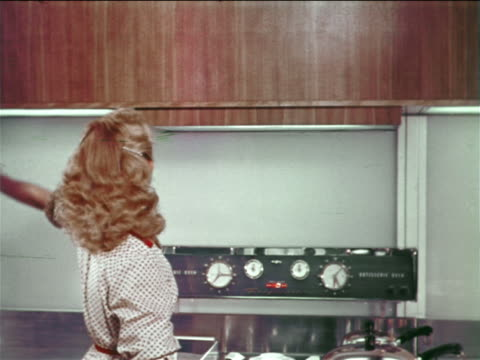 1954 teen girl/woman waves hand + shelf of dishes automatically lowers above stove in kitchen - 1954 stock videos and b-roll footage
