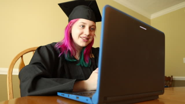 teen graduate in cap and gown video chatting - pink hair stock videos & royalty-free footage
