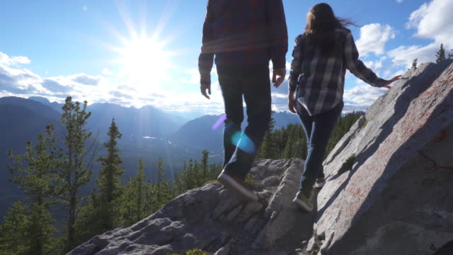 teen hikers traverse rock ridge above valley, sunrise - checked pattern stock videos & royalty-free footage