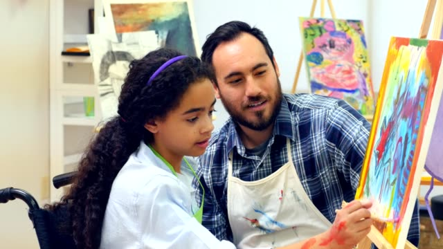teen in wheel chair paints with teacher during art class - art class stock videos & royalty-free footage