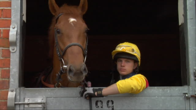 MS Teen jockey petting horse in stable / Newbury, England, UK
