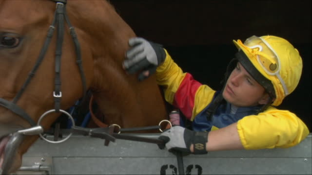 cu zo teen jockey petting horse in stable / newbury, england, uk - see other clips from this shoot 1045 stock videos and b-roll footage