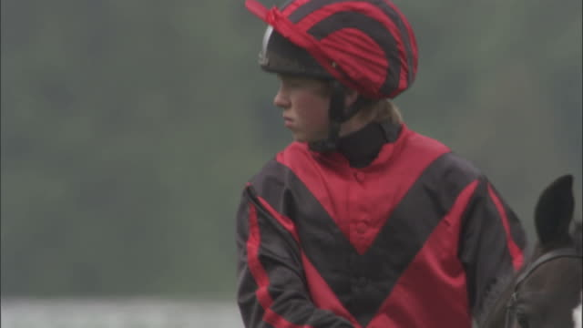 SLO MO CU TD Teen jockey riding on horseback at Newbury Racecourse / Newbury, England, UK