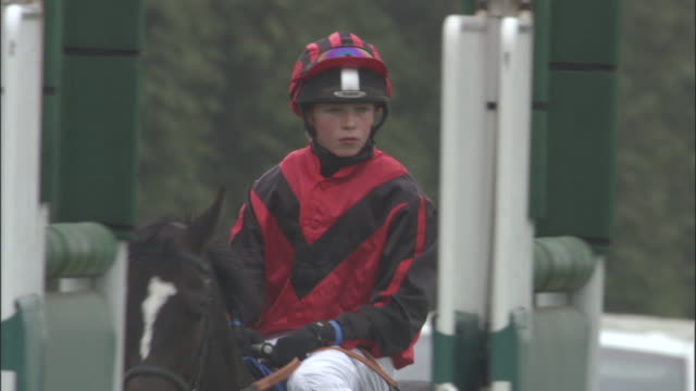 slo mo ms teen jockey riding on horseback behind gates at newbury racecourse / newbury, england, uk - newbury england stock videos & royalty-free footage