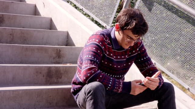 teen on cell phone - sweater stock videos & royalty-free footage