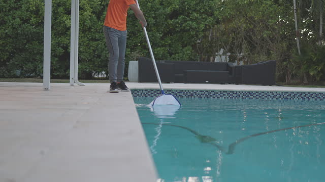 teen picking leaves and cleaning swimming pool in miami - one teenage boy only stock videos & royalty-free footage