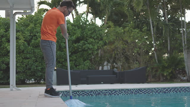 teen picking leaves and cleaning swimming pool - one teenage boy only stock videos & royalty-free footage