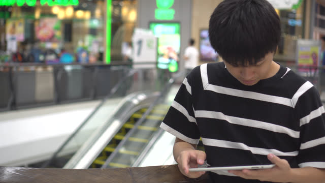 teen playing a tablet in a mall. - kindle stock videos & royalty-free footage