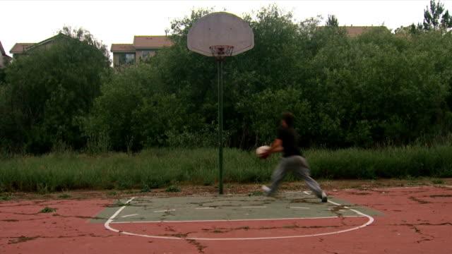 vídeos y material grabado en eventos de stock de adolescente jugando baloncesto de montaje - pistas