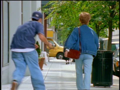 rear view teen purse snatcher grabbing purse of woman walking down sidewalk - thief stock videos & royalty-free footage