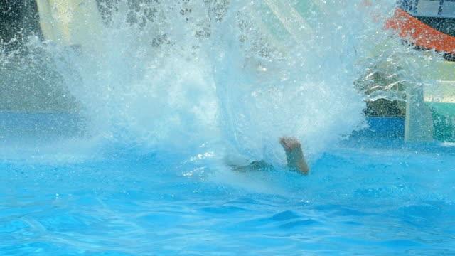 tonåring rider på vattenrutschbanorna i vattenparken (slow motion) - vattenrutschbana rutschkana bildbanksvideor och videomaterial från bakom kulisserna