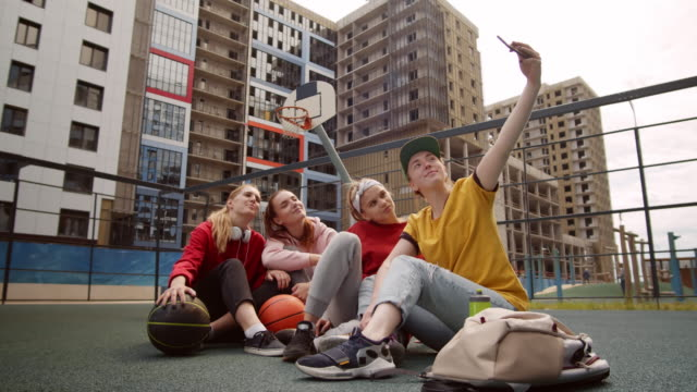 teen streetball team of girls sitting on court and taking selfie together - sitting on ground stock videos & royalty-free footage