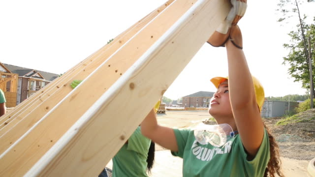 teen volunteers lifting construction framing - volunteer stock videos & royalty-free footage