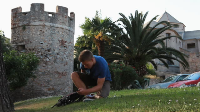 Teen walks across grass lawn below castle, begins texting