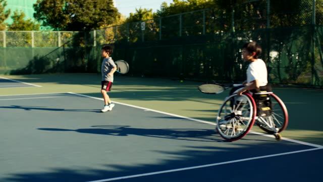 vídeos de stock e filmes b-roll de slo mo teenage adaptive tennis player playing doubles tennis - cadeira de rodas