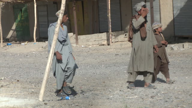 stockvideo's en b-roll-footage met a teenage afghan villager appears confused as he walks past u.s. marines. - afghanistan