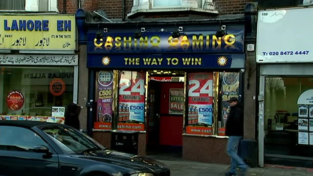 teenage amusement arcade armed robbers jailed london east ham 'casino gaming' shop on street 'play the latest slots' poster in window - casino poster stock videos & royalty-free footage