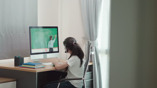 vidéos et rushes de une adolescente asiatique a étudié les mathématiques avec l'enseignant en ligne par ordinateur dans la chambre à coucher à la maison pendant l'enseignement à domicile tandis que l'école a été fermée en raison de l'épidémie covid-19. - person in education