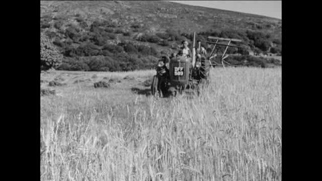 ws teenage backpackers watch farmers in a u.k. national park / uk - hay baler stock videos & royalty-free footage