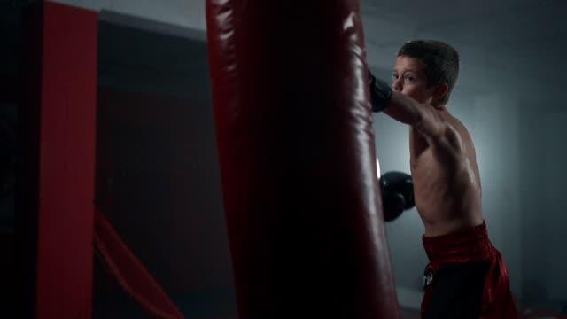 vídeos y material grabado en eventos de stock de boxeador adolescente golpeando una bolsa - un solo adolescente
