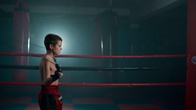 vídeos y material grabado en eventos de stock de entrenamiento de boxeador adolescente con cuerda de salto - un solo adolescente