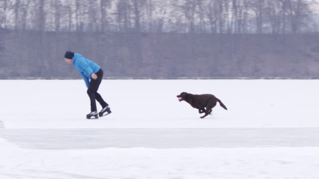 4K Teenage boy and dog ice skating and running on frozen lake, slow motion