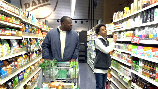 teenage boy and father shopping in supermarket - 14 15 years stock videos & royalty-free footage