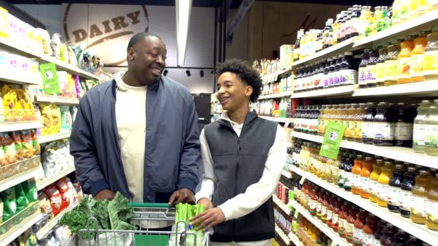 vídeos de stock e filmes b-roll de teenage boy and father shopping in supermarket - 14 15 years