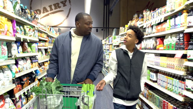 teenage boy and father shopping in supermarket - modern manhood stock videos & royalty-free footage