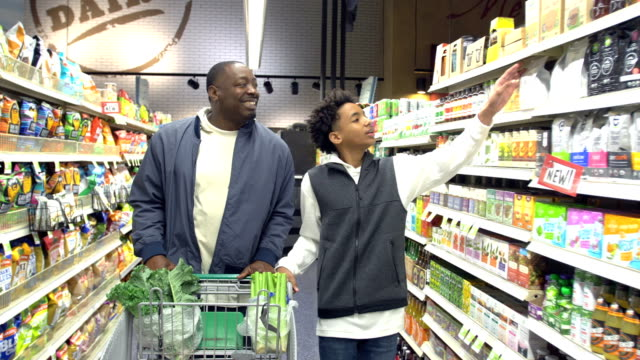 teenage boy and father shopping in supermarket - groceries stock videos & royalty-free footage