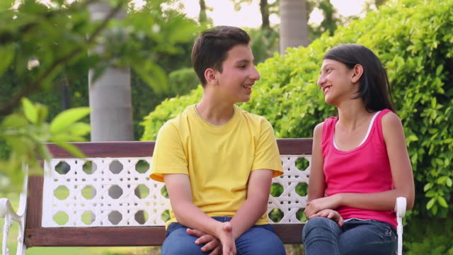 teenage boy and girl enjoying in the park, delhi, india - whispering stock videos & royalty-free footage