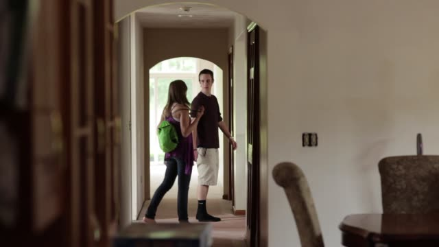Teenage boy and girl exploring a house