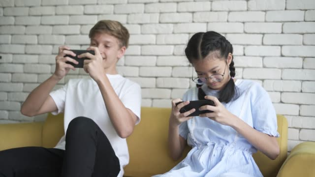 teenage boy and girl playing the video game on smart phone - brother stock videos & royalty-free footage