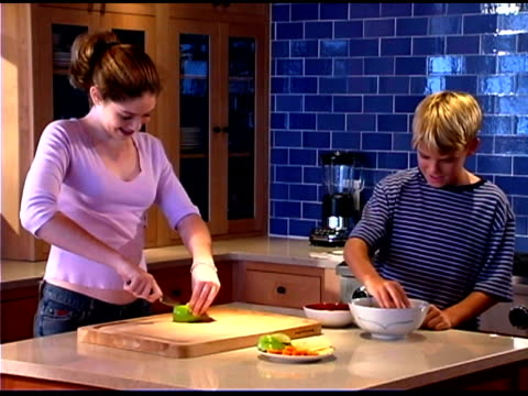 teenage boy and girl preparing food in kitchen - see other clips from this shoot 1335 stock videos and b-roll footage