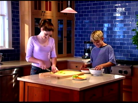 vidéos et rushes de teenage boy and girl preparing food in kitchen - 16 17 ans