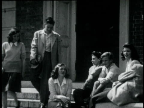 vídeos de stock e filmes b-roll de 1946 ws teenage boy and girl sit down to talk to a group of classmates on the steps in front of a school - sentar se