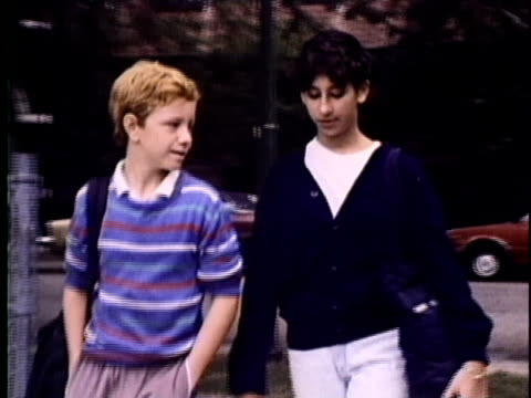 1986 MS Teenage boy and girl walking outdoors, girl smoking cigarette, USA, AUDIO
